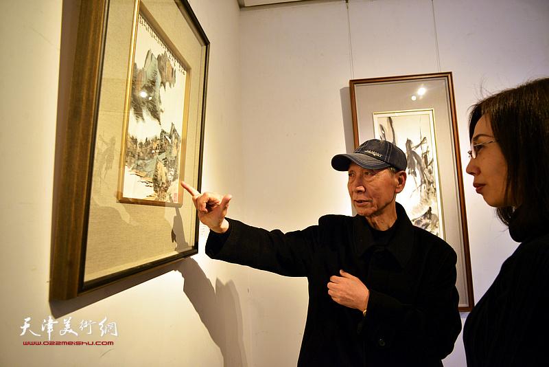 曹恩祥、张鸾在画展现场观赏梁崎先生画作。