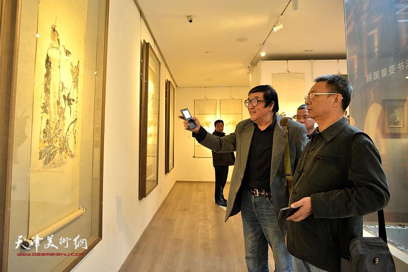 卢贵友、李金恒在画展现场观赏梁崎先生画作。