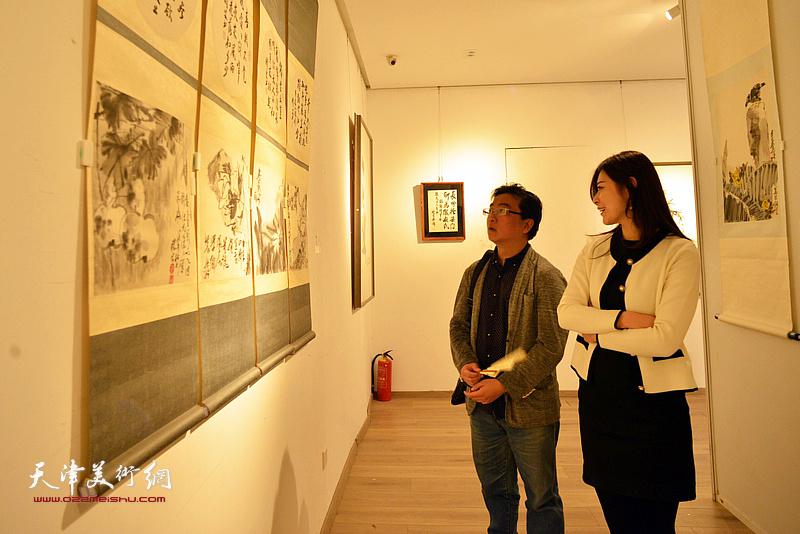 朱兆煜、宋晗在画展现场观赏梁崎先生画作。