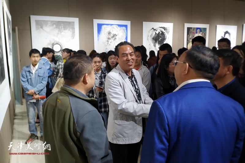 李寅虎在画展现场陪同嘉宾欣赏作品。