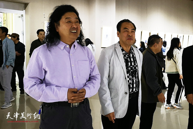 李寅虎在画展现场陪同上官超英欣赏作品。