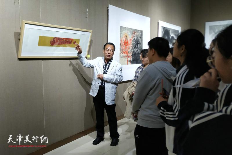 李寅虎在画展现场向学画的青年学生讲解作品。