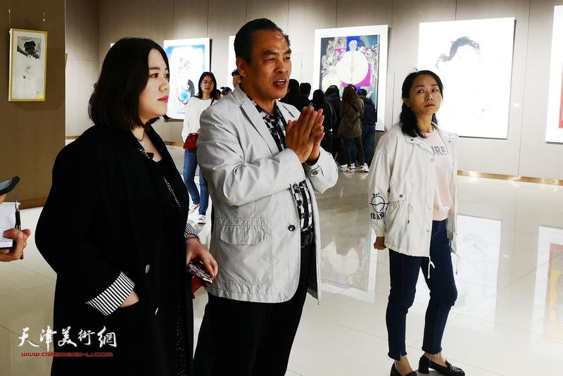 李寅虎在画展现场陪同嘉宾观赏作品。