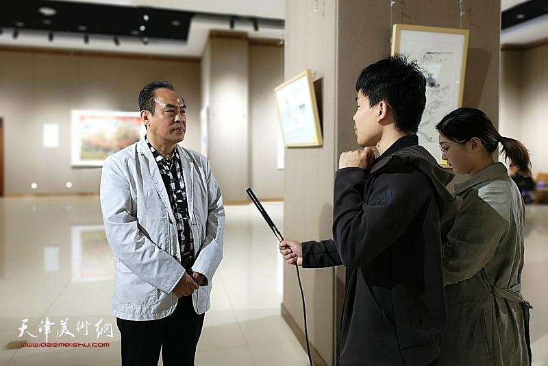 李寅虎在画展现场接受当地媒体的采访。