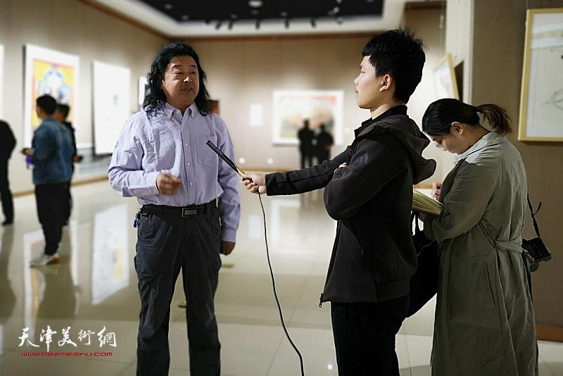 上官超英在画展现场接受当地媒体的采访。