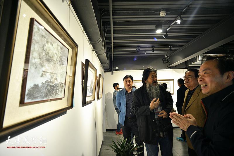 田贵明等在画展现场观看作品。