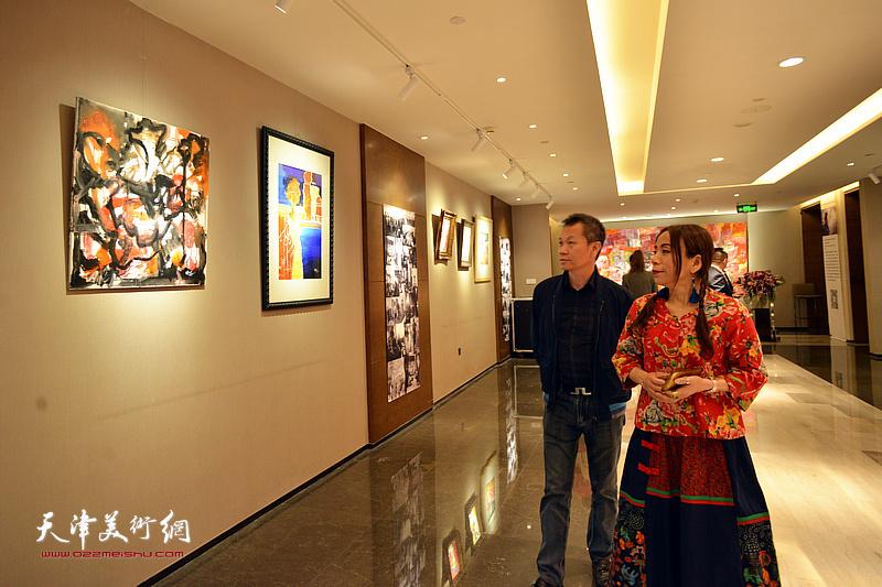 淋子陪同嘉宾观赏展出的画作。