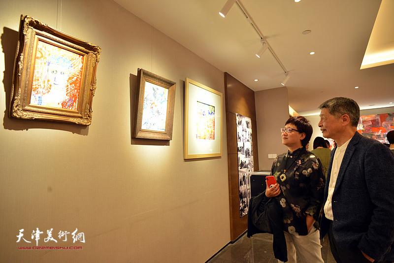 樊奇为、腾桓观赏展出的画作。