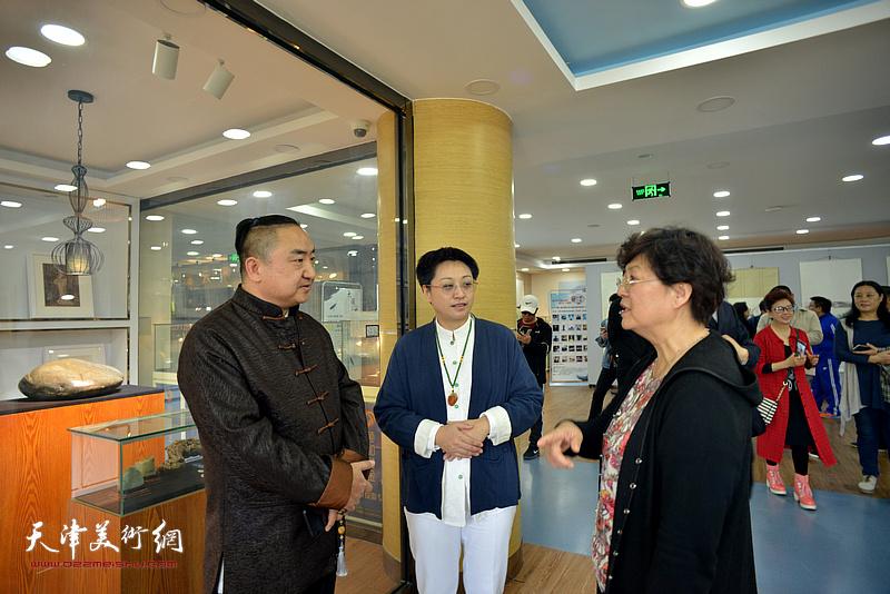 洪琴英、彭飞、苗栋在展览现场交流。