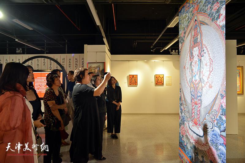 领导、嘉宾与观众观赏展出的唐卡艺术作品。