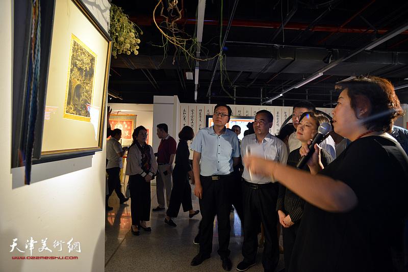阎妍为宋杨、曲维和、李孝辉等介绍展出的唐卡艺术作品。