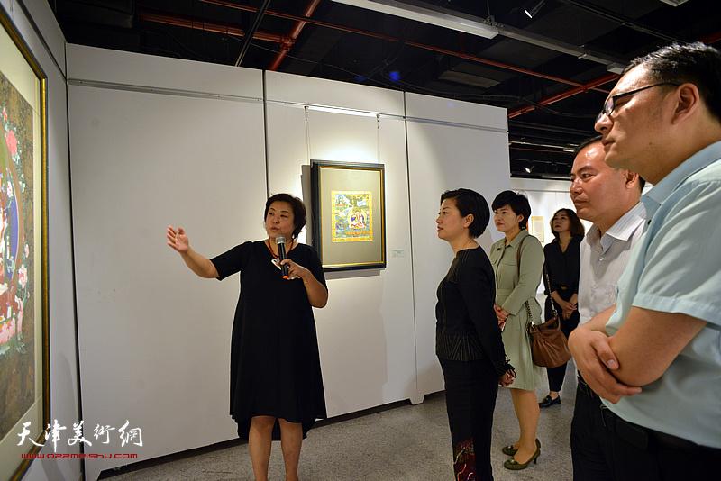 阎妍为宋杨、曲维和、李孝辉、李静等介绍展出的唐卡艺术作品。
