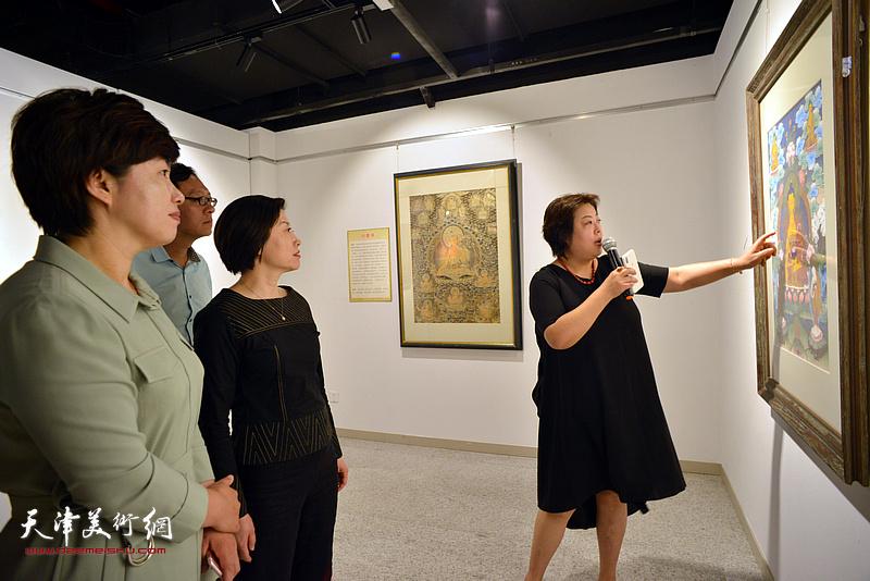 阎妍为宋杨、李孝辉、李静等介绍展出的唐卡艺术作品。