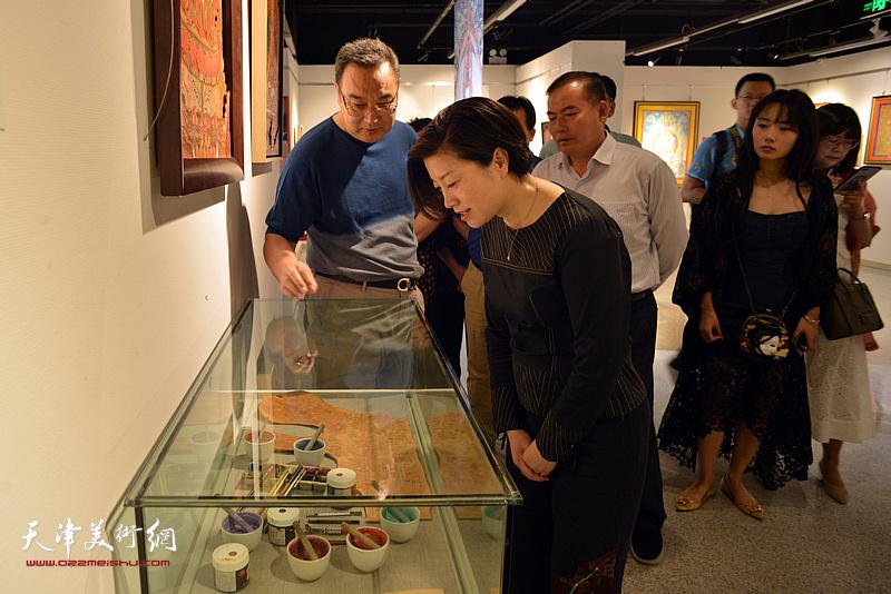梁利爽为宋杨、曲维和等介绍展出的唐卡艺术作品。