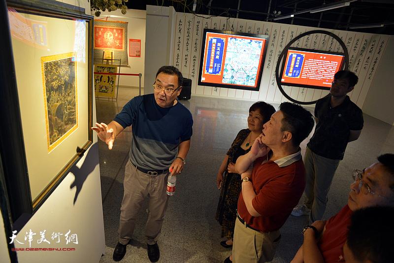 梁利爽为嘉宾、观众介绍展出的唐卡艺术作品。