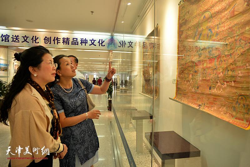 谭垚文为嘉宾介绍展出的唐卡艺术作品。