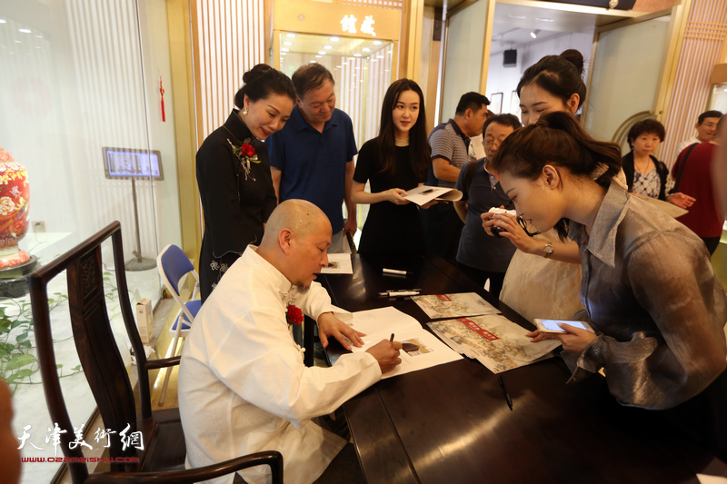 缪文杰先生在书画展现场为观众签名赠书。