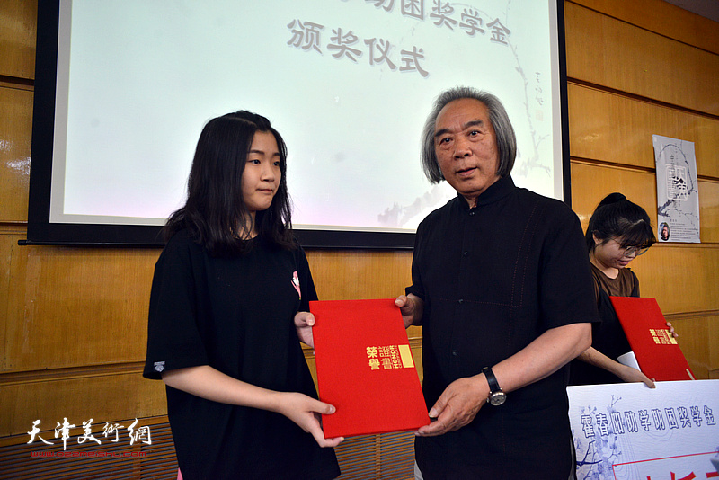 霍春阳先生为获得助学金的林妍同学颁奖。