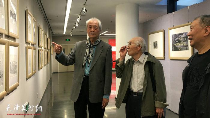 左起:王仲、郭文伟、陈明在观看写生作品。