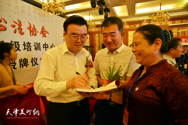 张华庆在揭牌仪式现场为来宾签名留念。