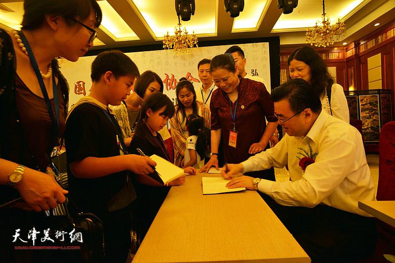 张华庆在揭牌仪式现场为小朋友签名留念。