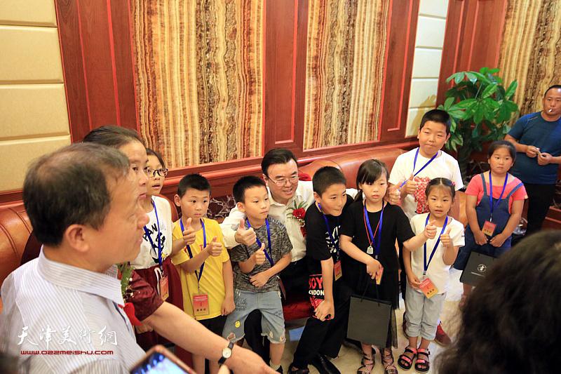 张华庆、赵洪生、王丽荣与喜爱硬笔书法艺术的小朋友在揭牌仪式现场。
