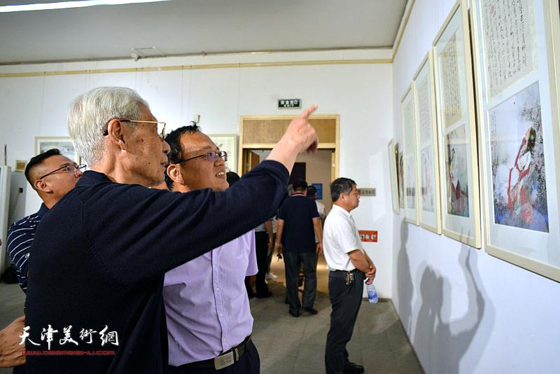 杨德树在画展现场向来宾介绍展出的作品。