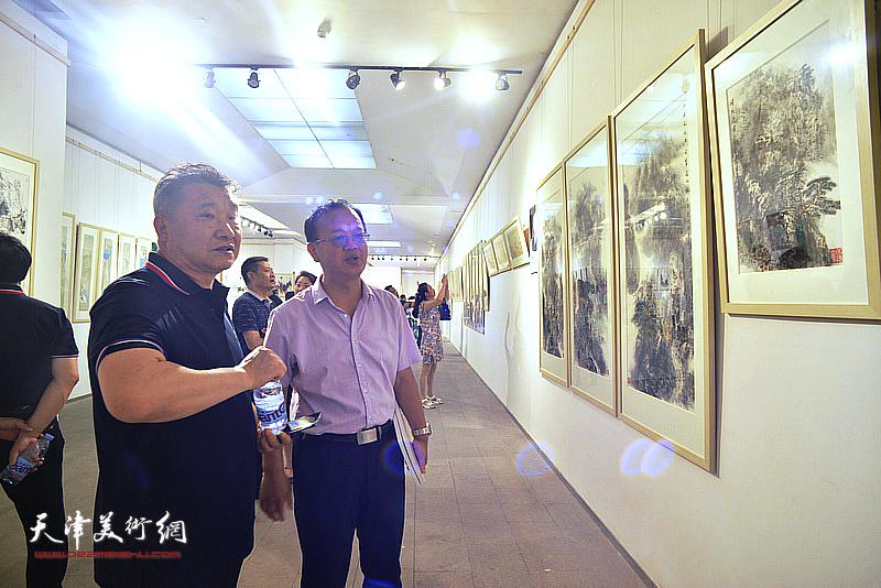 皮志刚在画展现场与当地书画爱好者交流。