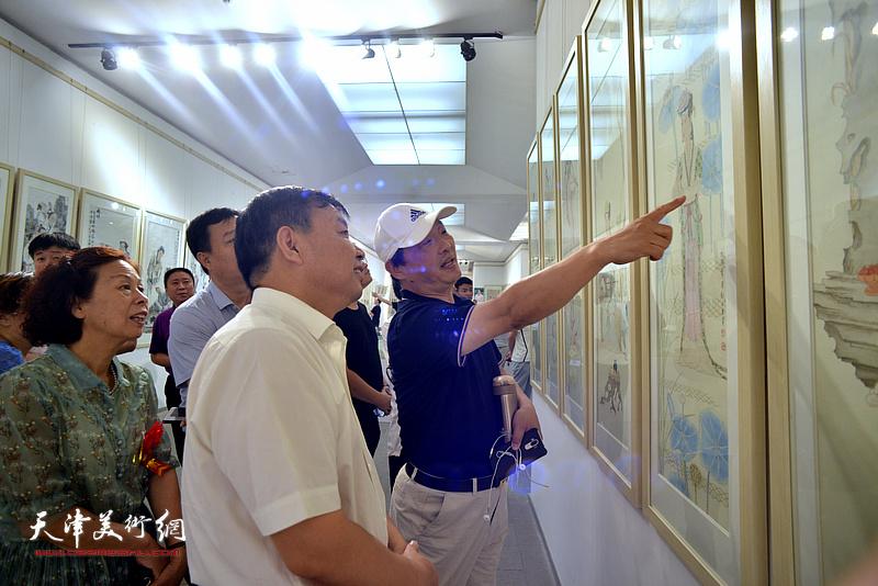 刘志君在画展现场向高唐的嘉宾介绍展出的作品。