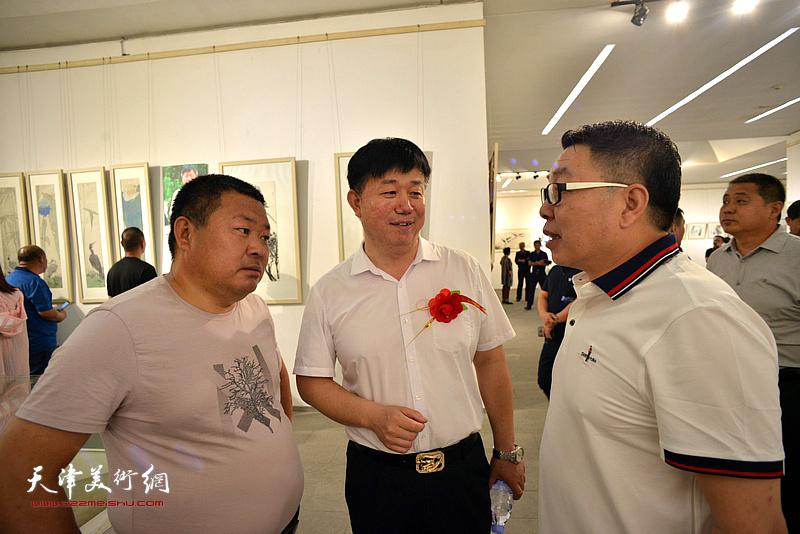 张维与邱玉广等在画展现场交流。