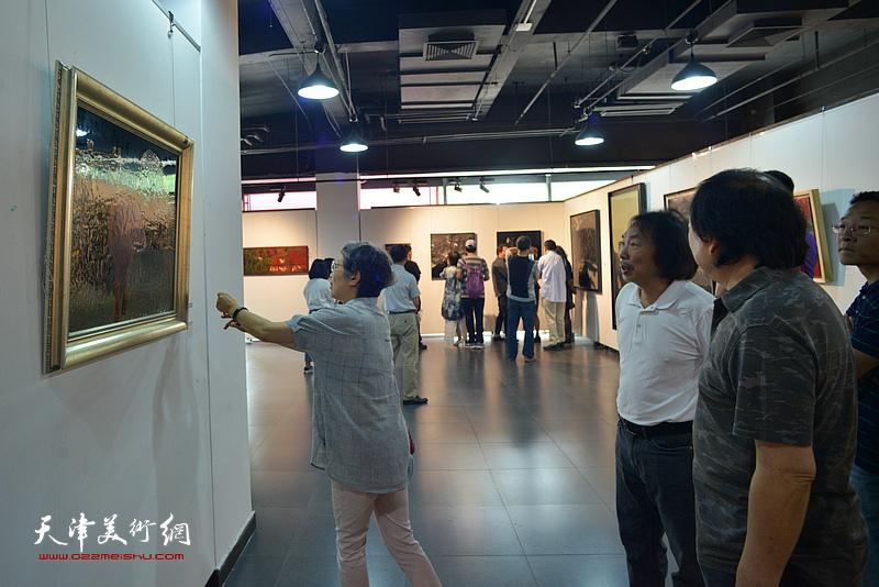 中国美协漆画艺委会陈金华主任观赏展出的作品。