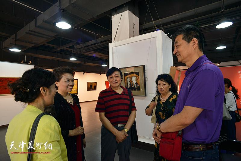 天津美协副主席琚俊雄与部分参展作者在画展现场交流。