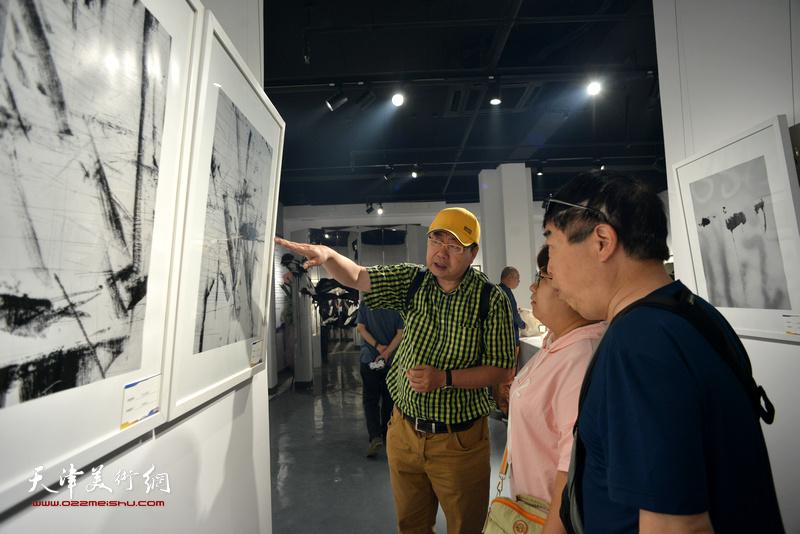 藏策向观众解读李维立影像作品。
