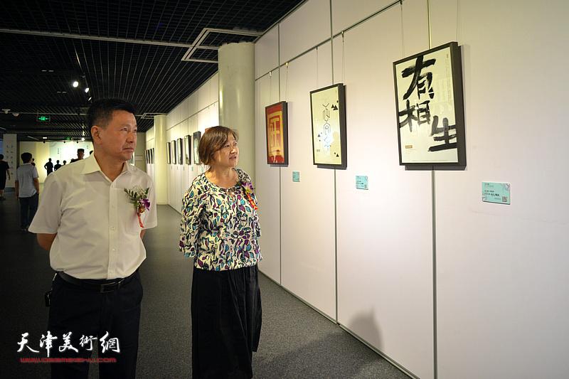 李岩、乔银萍观赏展出的设计作品。
