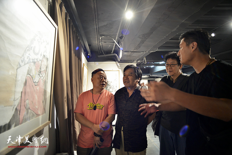 李耀春、晏平、吕大江、于露在画展现场观看画作。
