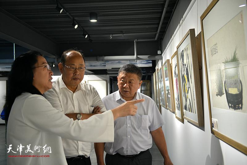 元林在画展现场向嘉宾介绍展出的作品。