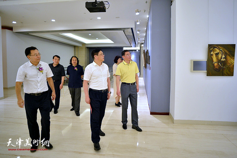 徐里、贾广健、张桂元、王卫平在画展现场观看作品。
