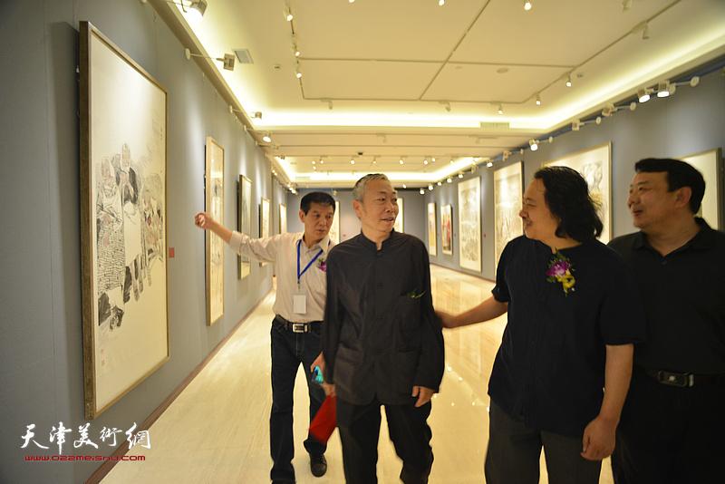 李翔、贾广健、范扬、王卫平在画展现场观看作品。
