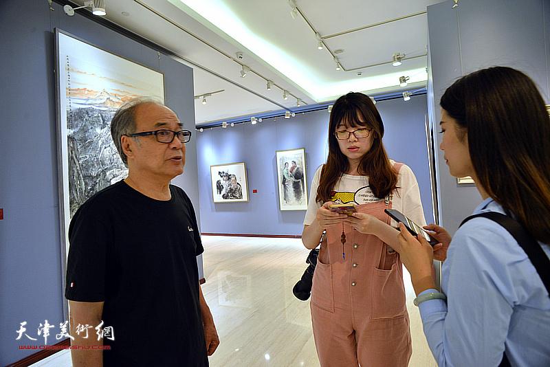 著名花鸟画家郭书仁在画展现场接受媒体采访。