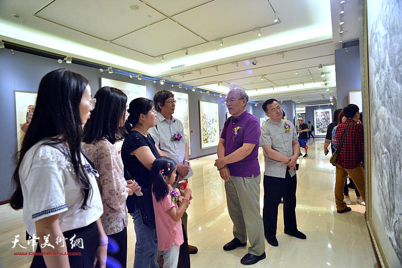 何延喆与青年画家在画展现场交流。