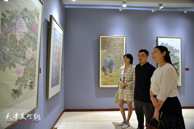 赵红云、田怀良、蒋晓溪在画展现场观看作品。
