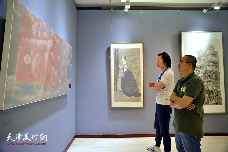 颜萌、汪洋在画展现场观看作品。