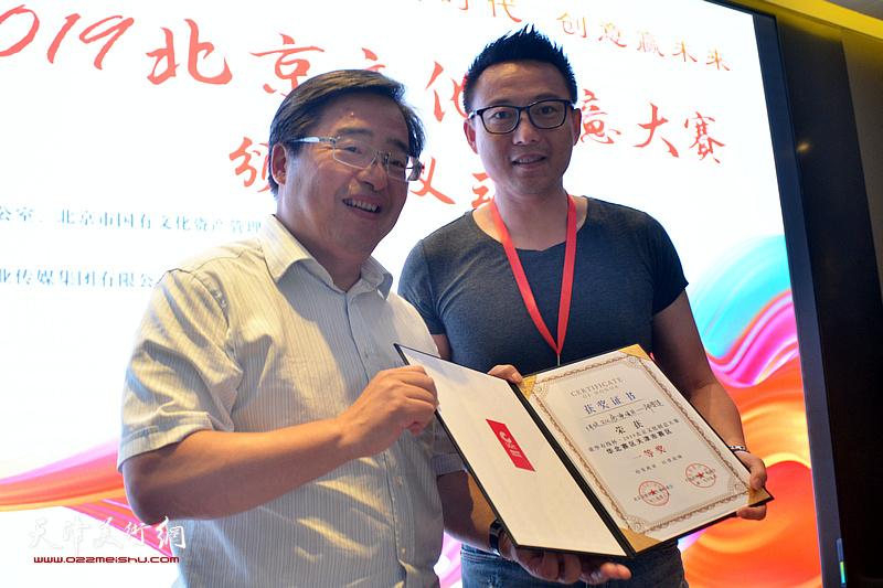 """中共北京市委宣传部副巡视员、北京市文化创意产业促进中心主任梅松为获得一等奖的《传统文化展演项目——""""神兽集""""》颁奖。"""