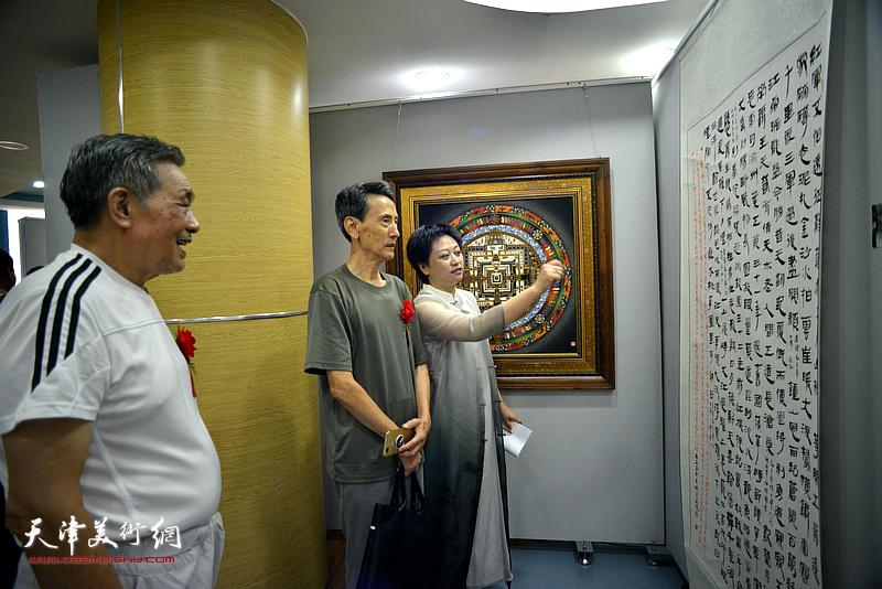 彭飞向李文安、顾富林介绍展出的书画作品。