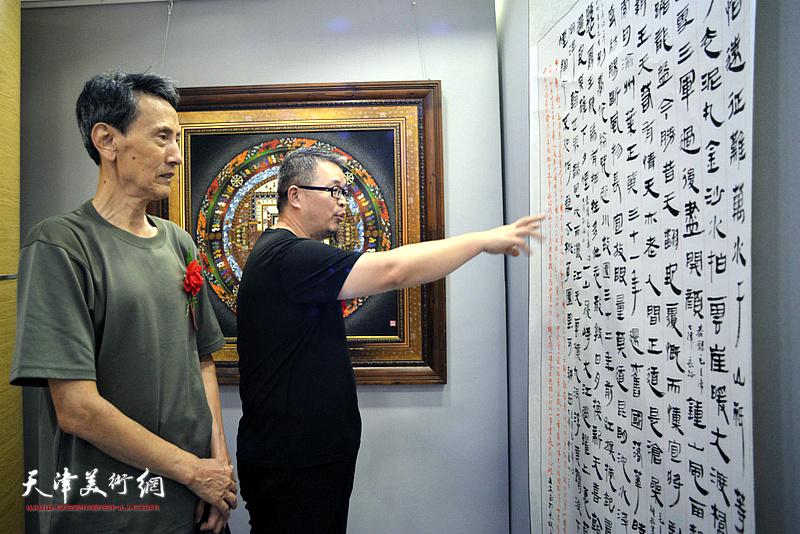 李文安、靳绍平观赏展出的书画作品。