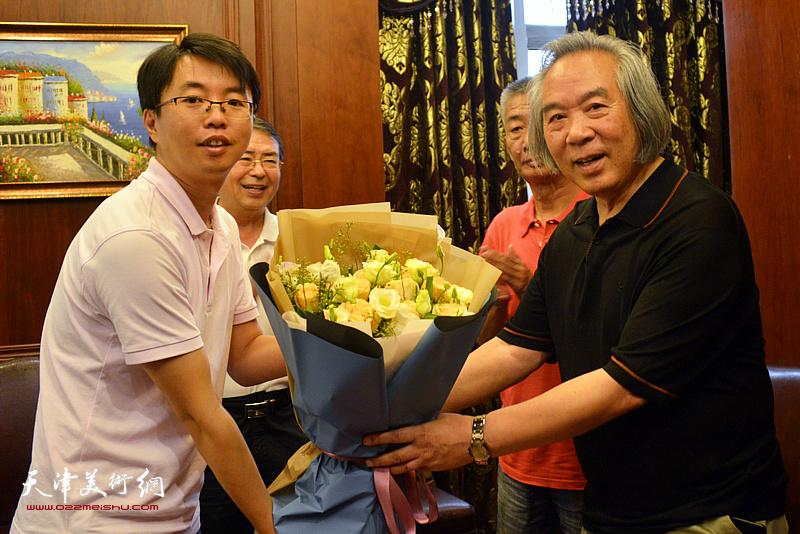 徐群向霍春阳教授敬献鲜花。