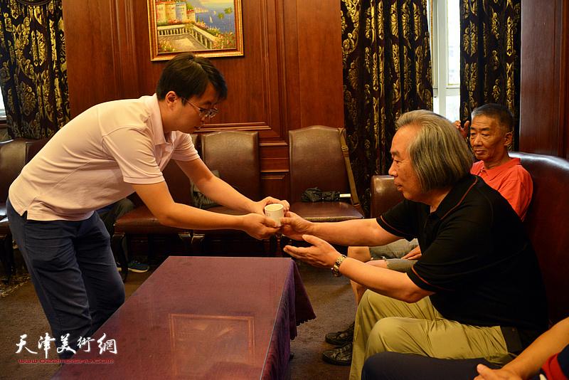 徐群向霍春阳教授敬茶。