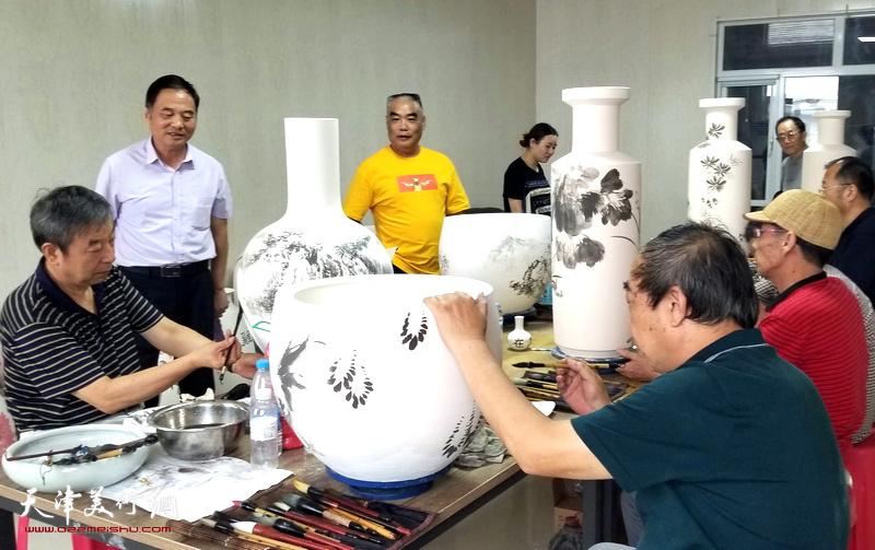 南开画院画家们在北方陶艺中心创作青花瓷作品。