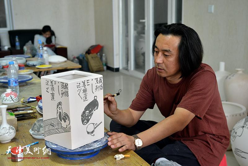 姜兴达在北方陶艺中心创作青花瓷作品。