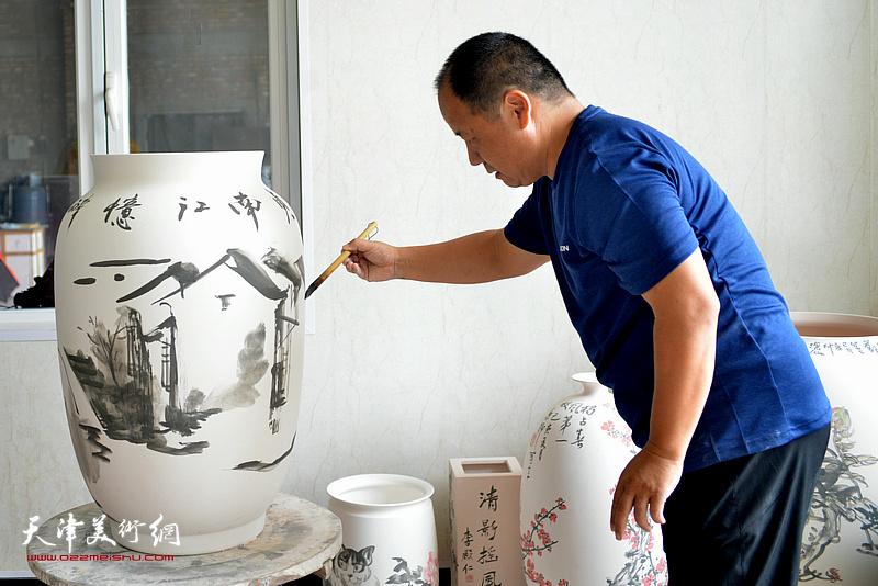 李思哲在北方陶艺中心创作青花瓷作品。
